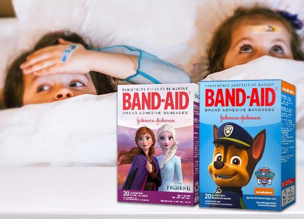 Deux boîtes de pansements Band-Aid pour enfants sur une image montrant deux enfants au lit