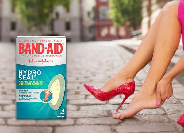Boîte de pansements Band Aid Hydro Seal sur une image montrant des jambes de femmes et une chaussure rouge